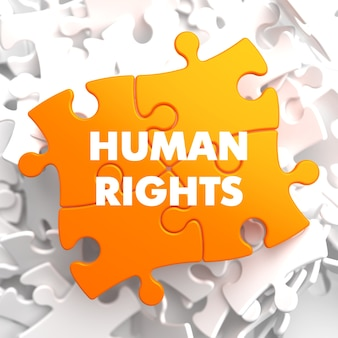 Prawa człowieka na pomarańczowej łamigłówce na białym tle.