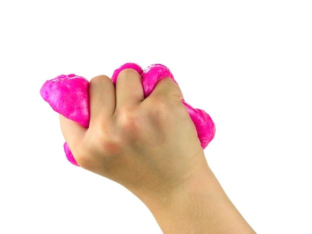 Prawa ręka dziecka mocno ściska czerwony śluz na białej powierzchni. zabawka antystresowa. zabawka rozwijająca motorykę dłoni.