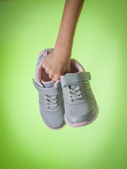 Prawa ręka dziecka trzyma modne damskie trampki na zielonym tle. buty sportowe. trend kolorystyczny.