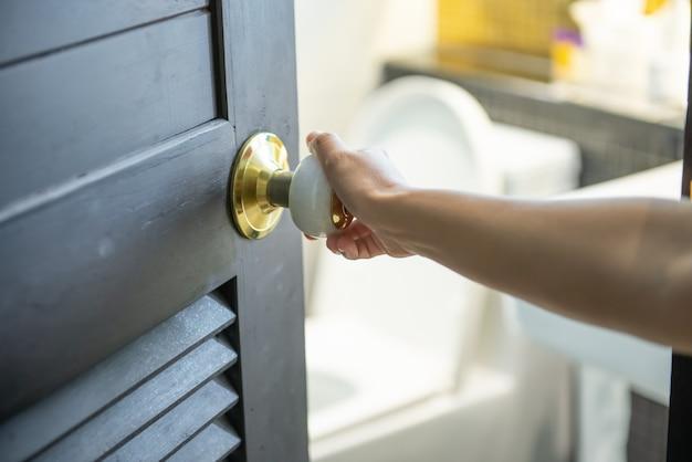 Prawa ręka kobiety, która otworzyła drzwi do toalety