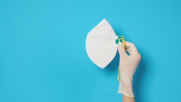 Prawa ręka z białą rękawiczką i maską n 95 chroniącą przed infekcją wirusową. umieść na niebieskim tle.
