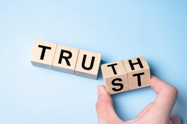 Prawda zamiast zaufania. ręka obraca kością i zmienia słowo zaufanie na prawdę.