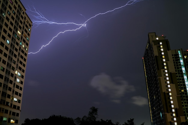 Prawdziwa błyskawica błyskuje w nocnym niebie nad wysokimi budynkami bangkok, tajlandia