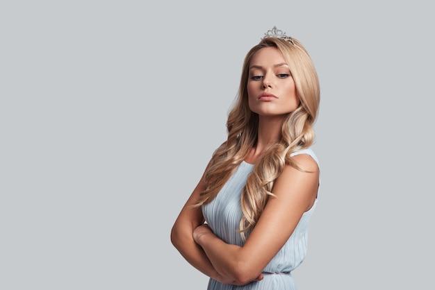 Prawdziwa królowa. dumna młoda kobieta w koronie trzymająca skrzyżowane ręce, stojąc na szarym tle