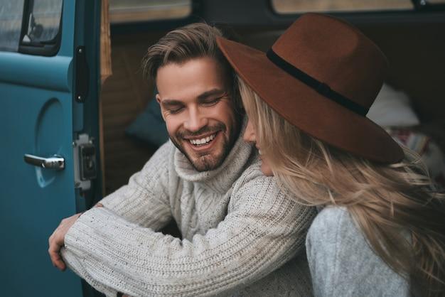 Prawdziwa miłość. piękna młoda para uśmiecha się siedząc w niebieskim mini vanie w stylu retro