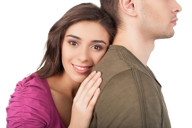 Prawdziwa miłość. wesoła młoda kobieta przytulająca swojego chłopaka i patrząca w kamerę stojąc na białym tle
