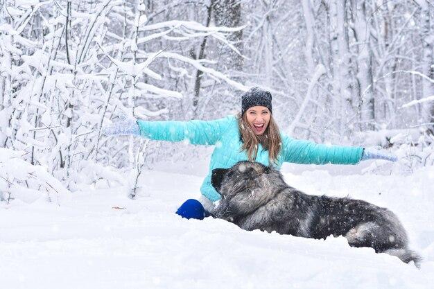 Prawdziwa śnieżna zima. kobieta z dużym psem w śniegu. przyjaźń człowieka z psem.