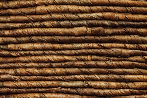 Prawdziwa stara tekstura brązowego kosza z luźnymi nitkami. tło rzemiosło tkackie. powierzchnia kosza na gałązki.