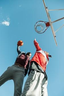 Prawdziwa walka. niski kąt sympatycznych młodych mężczyzn podskakujących podczas walki o piłkę