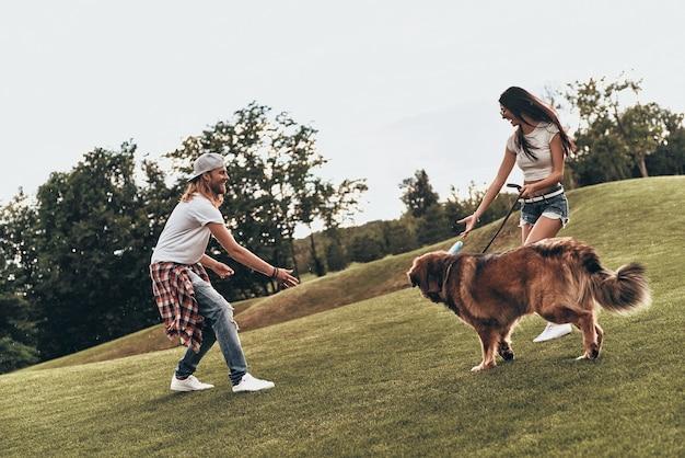 Prawdziwa zabawa. pełna długość pięknej młodej pary bawiącej się z psem podczas spędzania czasu na świeżym powietrzu