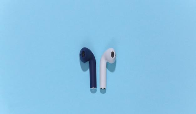 Prawdziwe bezprzewodowe słuchawki bluetooth lub wkładki douszne na jasnoniebieskim tle
