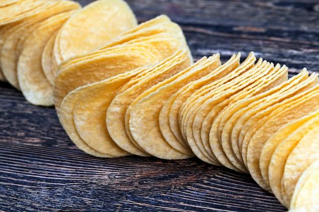 Prawdziwe chipsy ziemniaczane, zbliżenie żółtych złotych chipsów, wysokokaloryczne jedzenie, prawdziwe i chrupiące frytki