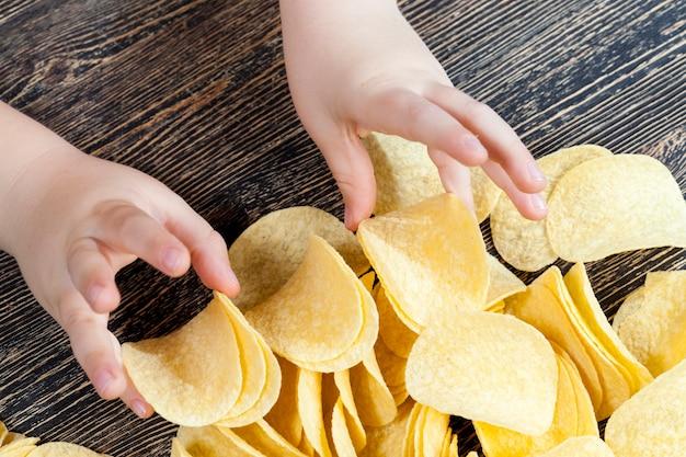 Prawdziwe chrupiące i słone chipsy ziemniaczane gotowe do spożycia, zbliżenie niezdrowych produktów spożywczych
