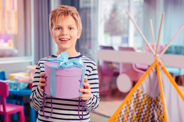 Prawdziwe emocje. szczęśliwe dziecko jest w swoim pokoju, patrząc prosto w kamerę