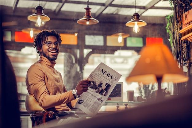 Prawdziwe emocje. zadowolony brodaty mężczyzna z uśmiechem na twarzy siedząc z gazetą w rękach
