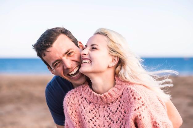 Prawdziwe i prawdziwe szczęście tych młodych pięknych ludzi ma twarz miłej blondynki i uroczego czarnowłosego faceta z wielkim uśmiechem i śmiechem z oceanem i plażą, miejsce na letnie chwile