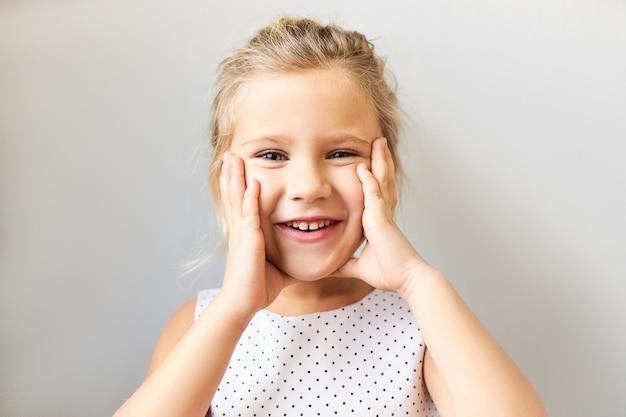 Prawdziwe ludzkie reakcje i uczucia. portret pięknego, słodkiego chłopca w sukience w kropki, trzymającego ręce na jej pulchnych policzkach, cieszącego się radosnym wyrazem twarzy, podekscytowany prezentem urodzinowym
