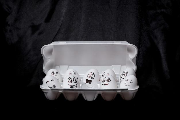 Prawdziwe ręcznie malowane jajka. białe jajka z rysowanymi twarzami ułożone w kartonie.