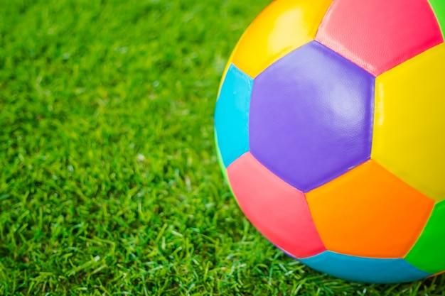 Prawdziwe skórzana kolorowe wielokolorowy piłka nożna na zielonej trawie.