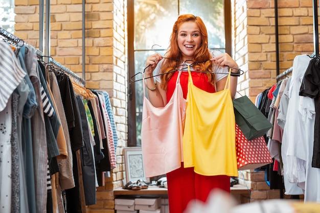 Prawdziwe szczęście. emocjonalna młoda dziewczyna czuje się szczęśliwa i radośnie się uśmiecha podczas wizyty w modnym sklepie z ubraniami i przyciskania do piersi dwóch bluzek