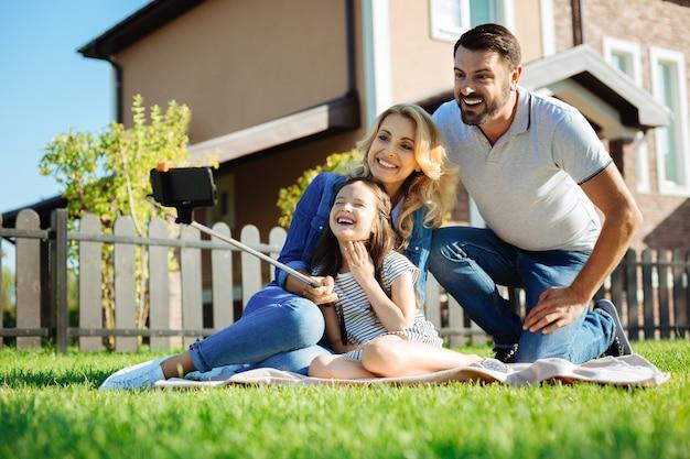 Prawdziwe szczęście. szczęśliwa śliczna mała dziewczynka siedzi na dywanie obok swojego ojca i matki i robi selfie swojej rodziny, podczas gdy wszyscy uśmiechają się szeroko