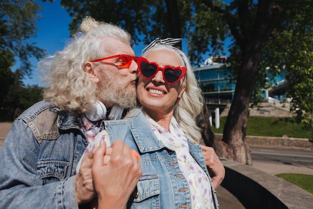 Prawdziwe uczucia. zachwycony brodaty mężczyzna całuje swoją żonę, okazując jej swoje uczucia