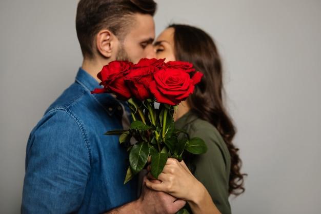 Prawdziwe uczucia. zbliżenie uroczej pary w swobodnych strojach, która podczas całowania chowa się za bukietem czerwonych róż.