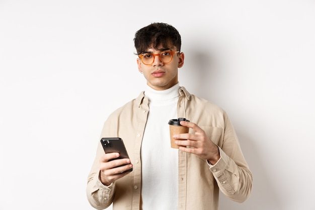 Prawdziwi ludzie. stylowy hipster facet w okularach, trzymając filiżankę kawy z kawiarni na wynos i telefon komórkowy, stojąc na białej ścianie.