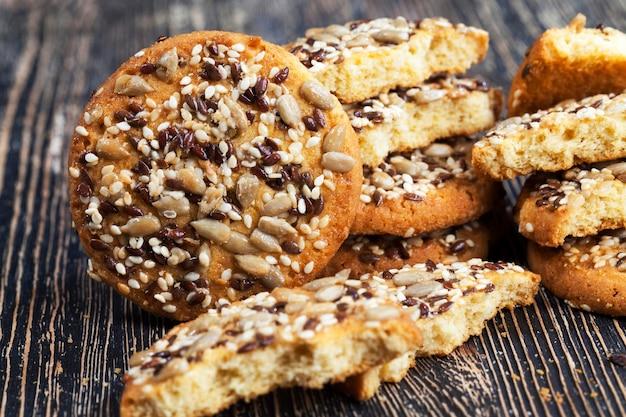 Prawdziwie smaczne i świeże ciasteczka owsiano-pszenne posypane różnymi rodzajami orzechów i nasion
