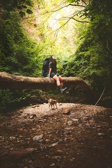 Prawdziwy i naturalny turysta odpoczywający na zwalonym drzewie i uśmiechnięty.