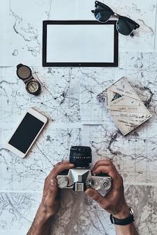 Prawdziwy podróżnik. bliska widok z góry mężczyzny trzymającego aparat fotograficzny ze smartfonem, okulary przeciwsłoneczne