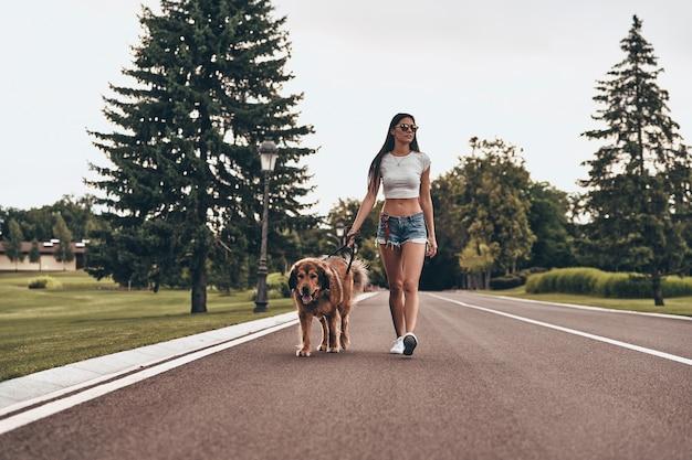 Prawdziwy przyjaciel. pełna długość pięknej młodej kobiety spacerującej z psem podczas spędzania czasu na świeżym powietrzu