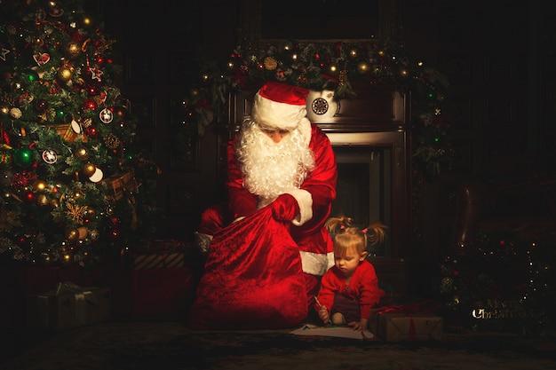 Prawdziwy święty mikołaj bawi się z dziećmi w pobliżu choinki.