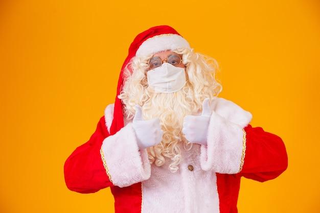 Prawdziwy święty mikołaj na żółtym tle, noszący maskę ochronną przed covid19. boże narodzenie z dystansem społecznym. covid-19