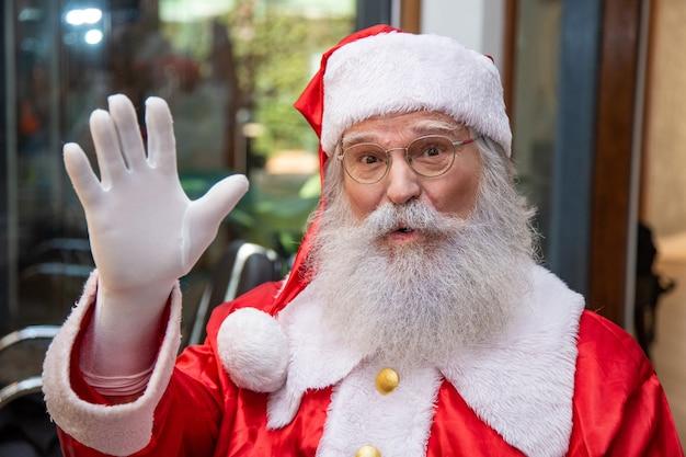 Prawdziwy święty mikołaj w okularach, rękawiczkach i kapeluszu patrzący prosto w obiektyw. ścieśniać. prawdziwy święty mikołaj patrzący w kamerę
