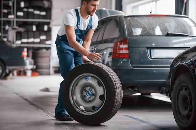 Prawie na miejscu. pracownik w niebieskim mundurze pracuje w salonie samochodowym
