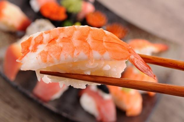 Prawn sushi trzymane przez pałeczki