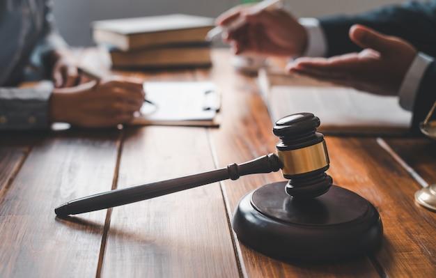 Prawnicy rozmawiają przy tablecie z sędziowskim młotkiem