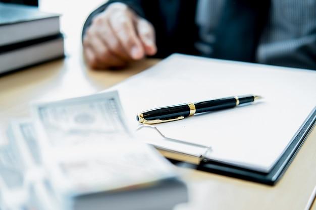 Prawnik biznesmen w garniturze ukrywa pieniądze. łapówka w formie banknotów dolarowych.