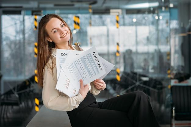 Prawnik korporacyjny w miejscu pracy. uśmiechnięta młoda kobieta siedzi na biurku z garstką kontraktów.