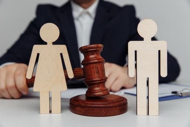 Prawnik lub doradca trzyma młotek za postaciami młodych rodzin rozwodu lub koncepcji separacji
