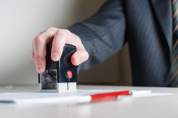 Prawnik lub notariusz umieszcza pieczęć na dokumencie. znaczek w dłoni mężczyzny.