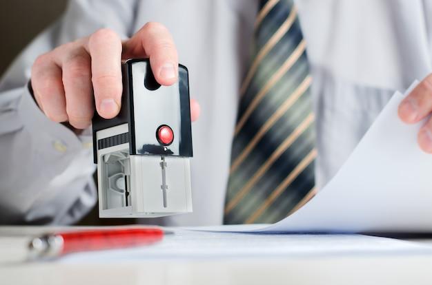 Prawnik lub notariusz umieszcza pieczęć na dokumencie.