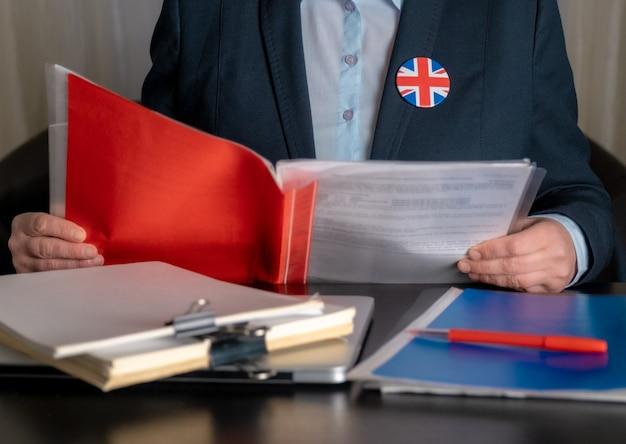 Prawnik lub pracownik biurowy lub urzędnik służby cywilnej w pobliżu miejsca pracy z flagą wielkiej brytanii na ikonie kurtki