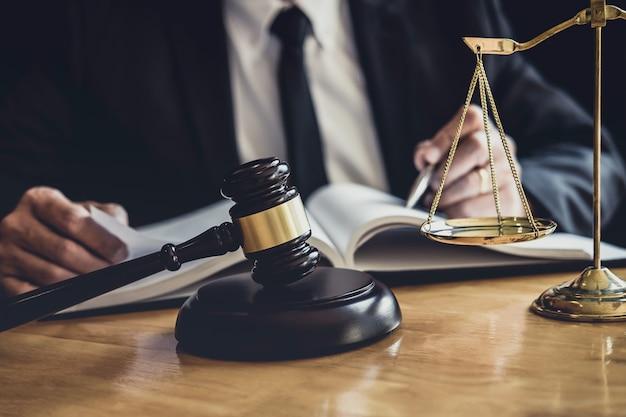 Prawnik lub sędzia pracujący z dokumentami kontraktowymi, książkami prawnymi i drewnianym młotkiem na stole w sali sądowej