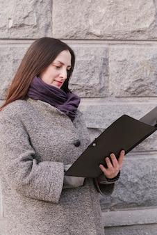 Prawnik na zewnątrz patrząc na folder