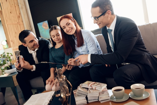 Prawnik pokazuje kobiecie, gdzie musi się podpisać, aby otrzymać pieniądze.