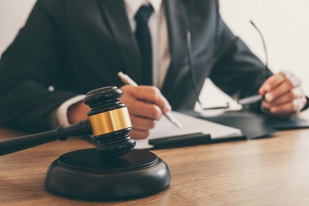 Prawnik pracujący nad dokumentami i raportem z ważnej sprawy oraz drewnianym młotkiem