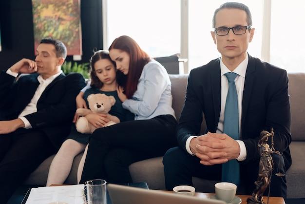 Prawnik siedzi na kanapie obok zdenerwowanej rodziny.