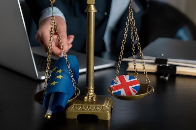 Prawnik stawia na wadze flaga unii europejskiej i wielkiej brytanii na ikonie kurtki razem na wadze.